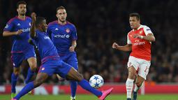 Penyerang Arsenal, Alexis Sanchez berebut bola dengan striker Olympiacos, Seba pada laga Liga Champions di Stadion Emirates, Inggris, Rabu (30/9/2015). (AFP Photo/Glyn Kirk)