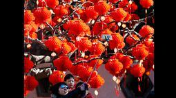Salah satu keluarga saat berfoto di depan pohon yang dihiasi lampion dari perayaan Tahun Baru Cina di Ditan Park, Beijing (18/2/2015). Tahun Baru Imlek pada 19 Februari akan menyambut Tahun Domba. (Reuters /Kim Kyung-Hoon)