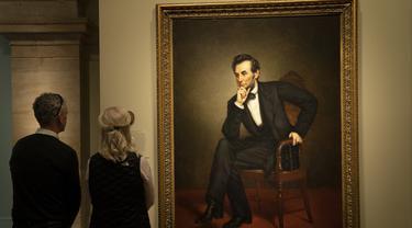 """Pengunjung mengamati lukisan mantan presiden Amerika Serikat Abraham Lincoln dalam pameran bertajuk """"Presiden-Presiden Amerika"""" (America's Presidents) di Galeri Potret Nasional di Washington DC, Amerika Serikat (17/2/2020). (Xinhua/Liu Jie)"""