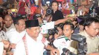 Prabowo berjalan menyusuri lapak pedagang sambil dikerumuni oleh ajudan dan wartawan. (Liputan6.com/Johan Tallo)