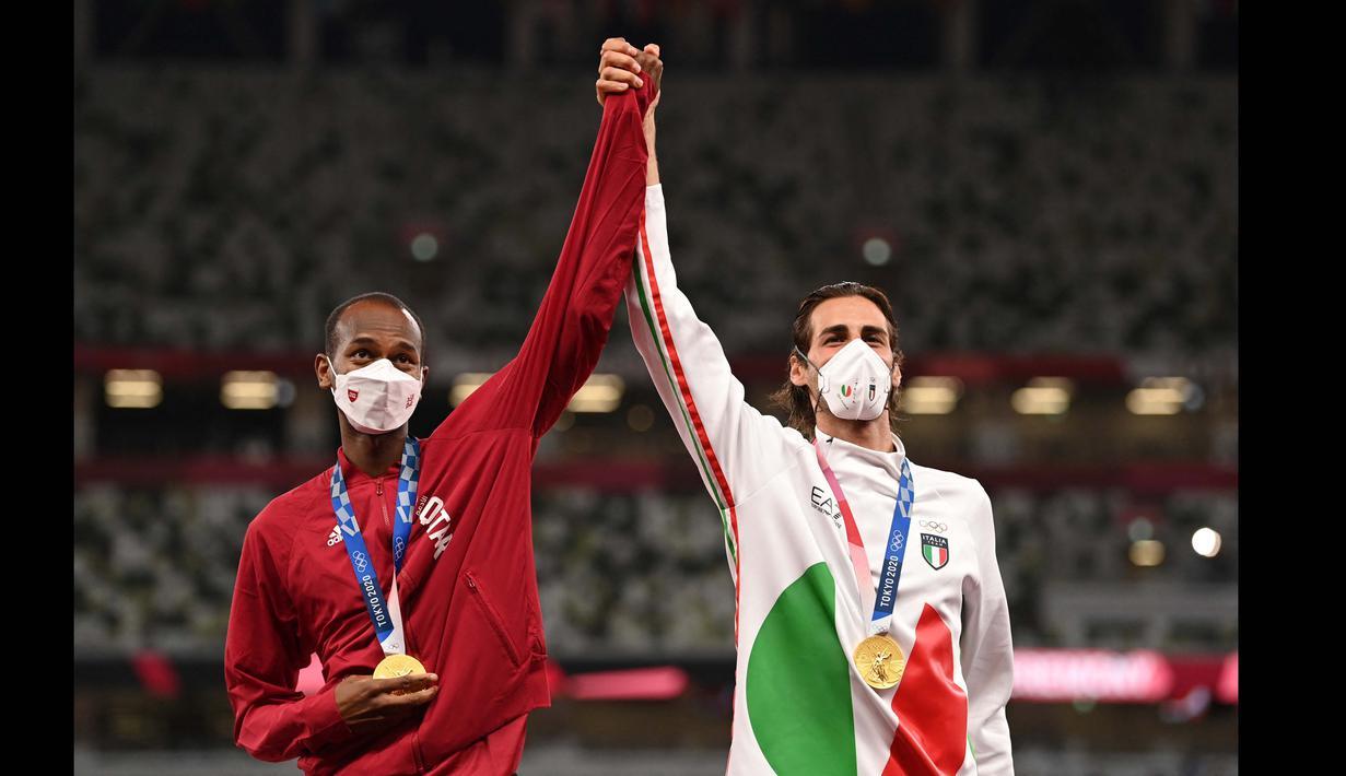 Atlet Qatar, Mutaz Barshim dan atlet asal Italia, Gianmarco Tamberi harus berbagi medali emas nomor lompat tinggi putra Olimpiade Tokyo 2020 di Olympic Stadium, Minggu (1/8/2021). (Foto: AFP/Ina Fassbender)