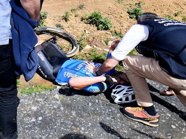 Pembalap sepeda Belgia, Michael Goolaerts mendapatkan pertolongan setelah terjatuh pada balapan klasik Paris-Roubaix di Prancis Utara, Minggu (8/4). Goolaerts meninggal setelah terkena serangan jantung saat balapan tersebut. (DAVID STOCKMAN/Belga/AFP)