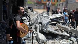 Penampilan seorang penyanyi Palestina selama acara musik di puing-puing bangunan yang baru-baru ini hancur oleh serangan udara Israel di kota Gaza, Selasa (14/5/2019). Aksi itu untuk menyerukan pemboikotan terhadap Kontes Lagu Eurovision 2019 yang diselenggarakan di Israel. (REUTERS/Mohammed Salem)