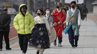 Pengunjung mengenakan masker berjalan di dekat Gwanghwamun, gerbang utama Istana Gyeongbok abad ke-14, dan salah satu landmark terkenal Korea Selatan, di Seoul, Sabtu (22/2/2020). Korsel pada hari Sabtu melaporkan lonjakan enam kali lipat infeksi virus dalam empat hari ke 346. (AP Photo/Lee Jin-man)