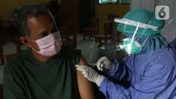 Tenaga kesehatan menyuntikan vaksin kepada warga di MTs As-Syafiiyah, Cilangkap, Jakarta, Kamis (3/6/2021). Vaksinasi akan menyasar sekitar 400 warga RT 03 RW 03 Cilangkap. (Liputan6.com/Herman Zakharia)