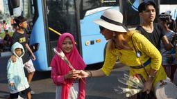 Sejumlah relawan membagikan bunga mawar ke warga saat berlangsungnya kegiatan car free day di kawasan Bundaran HI, Jakarta, Minggu (30/6/2019).  Aksi 1000 bunga mawar itu sebagai bentuk rasa syukur atas kemenangan pasangan Jokowi-Ma'ruf Amin di Pilpres 2019. (Liputan6.com/Immanuel Antonius)