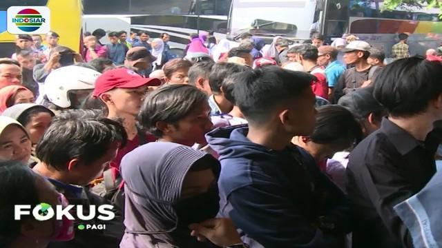 Para penumpang terlihat mengantre di depan loket perusahaan oto bus untuk mendapatkan tiket.