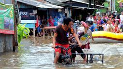 Hujan yang turun sejak Minggu (8/2) lalu, mengakibatkan kawasan perumahan mewah Garaharaya di Tangerang, Banten terendam air setinggi lebih kurang 90 cm. Tampak sejumlah bocah dievakuasi, Selasa (10/2/2015). (Liputan6.com/Faisal R Syam)