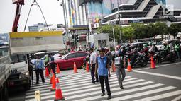 Petugas Dishub memindahkan separator beton untuk menutup sebagian jalan di depan kantor Bawaslu RI, Jakarta, Selasa (21/5/2019). Aparat kepolisian memperketat penjagaan gedung Bawaslu untuk aksi 22 Mei atau setelah penetapan hasil rekapitulasi suara Pemilu 2019 oleh KPU. (Liputan6.com/Faizal Fanani)