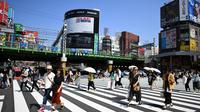 Sejumlah orang menggunakan payung dan topi untuk melindungi dirinya dari sinar matahari selama gelombang panas saat melintasi jalan di distrik Shinjuku Tokyo, Minggu (4/8/2019). Setelah menyerang beberapa wilayah di Eropa, suhu tinggi juga terjadi di Jepang. (Charly TRIBALLEAU / AFP)