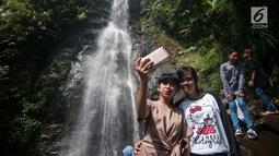 Wisatawan berswa foto di air terjun Cigentis, Kabupaten Karawang, Jabar, Kamis (29/6). Air terjun yang berada di kaki Gunung Sanggabuana tersebut menjadi salah satu tujuan wisata untuk mengisi libur lebaran. (Liputan6.com/Gempur M Surya)