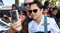 Seorang penggemar melakukan selfie dengan pembalap kawakan asal Tim Williams, Felipe Massa menjelang sesi latihan bebas pertama di Grand Prix Australia, Melbourne, Jumat (24/3). (AFP Photo/WILLIAM WEST)