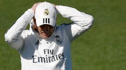 Pelatih Real Madrid Zinedine Zidane merapikan topinya saat menghadiri sesi pelatihan di fasilitas pelatihan Valdebebas di Madrid (15/3). Zidane kembali melatih Real Madrid menggantikan Santiago Solari. (AFP Photo/Gabriel Bouys)