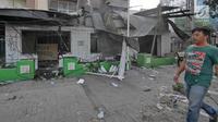 Pejalan kaki melintas di depan pos polisi yang rusak dibakar oleh massa di Jalan Agus Salim atau kawasan Sabang, Jakarta, Kamis (23/5/2019). Massa yang ricuh di depan Kantor Bawaslu, menghancurkan Pos Polisi Sabang serta membakar barang-barang yang ada di dalamnya. (Liputan6.com/Herman Zakharia)