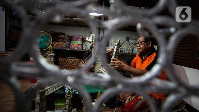Sugito (68) menyelesaikan pembuatan miniatur Monas dari kertas koran bekas di Bank Sampah Tri Alam Lestari, Pesanggrahan, Jakarta Selatan, Rabu (9/6/2021). Kemampuan untuk membuat kerajinan itu ia dapat secara otodidak. (Liputan6.com/Johan Tallo)
