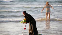 Seorang wanita muslim bermain di Pantai Laut Mediterania, Tel Aviv, Israel pada 22 Agustus 2016. Saat pengunjung pantai mengenakan busana yang minim mereka tetap mengenakan jilbab dan busananya. (REUTERS / Baz Ratner)