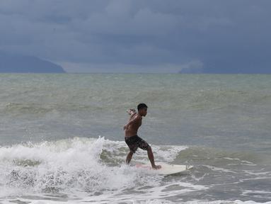 Abu Dzar Al-Ghifari berselancar ketika Gunung Krakatau (kiri) dan Anak Krakatau terlihat di lepas pantai Carita, Banten (26/12). Pemerintah meminta warga menghindari pantai di daerah-daerah tersebut. (AP Photo/Achmad Ibrahim)