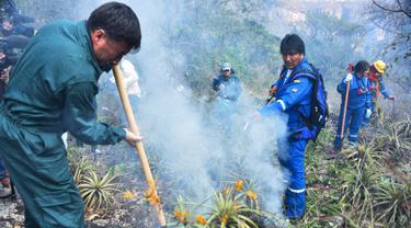 Presiden Bolivia Evo Morales (kanan) menyemprotkan air saat berusaha memadamkan api dalam kebakaran hutan di pinggiran Robore, Bolivia, Selasa (27/8/2019). Morales menunda kampanye pilpres untuk terjun langsung memadamkan api. (Raul Martinez/Bolivia's Communication Ministry press office via AP)