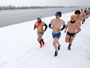 Para pelari ambil bagian dalam Underpants Run di tepi sungai Danube, Serbia pada 26 Januari 2019. Peserta berlari hanya dengan mengenakan pakaian dalam di tengah suhu yang mendekati 0 derajat Celcius. (AP/Darko Vojinovic)