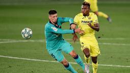 Bek Barcelona, Clement Lenglet, berebut bola dengan pemain Villareal, Samuel Chukwueze, pada laga La Liga di Stadion Estadio de la Ceramica, Minggu (5/7/2020). Barcelona menang 4-1 atas Villareal. (AFP/Jose Jordan)