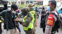 Anggota Satpol PP Kota Depok saat melakukan operasi masker di Kota Depok, Sabtu (26/12/2020). (Liputan6.com/Dicky Agung Prihanto)