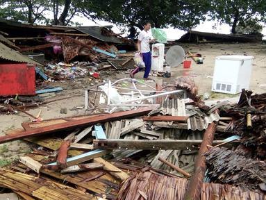Seorang pria mencari barang-barang dari rumahnya yang rusak setelah tsunami menerjang Pantai Carita, di perairan Banten, Minggu (23/12). Tsunami menerjang beberapa daerah di sekitar Selat Sunda pada Sabtu 22 Desember 2018 malam. (SEMI / AFP)