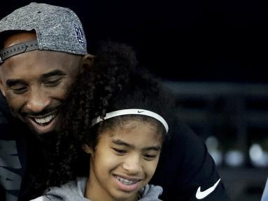 Pebasket NBA Kobe Bryant dan putrinya Gianna Bryant menonton pertandingan renang kejuaraan nasional AS di Irvine, California pada  26 Juli 2018. Kobe Bryant meninggal bersama putrinya Gianna yang berusia 13 tahun dalam kecelakaan helikopter di Calabasas, California. (AP Photo/Chris Carlson)
