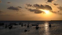 Nelayan mengayuh perahunya untuk pergi memancing ikan di Kedonganan, Denpasar, Bali (15/7/2019). Salah satu versi menyebutkan Kedonganan adalah sebuah desa yang sudah ada dari tahun 1324 (Saka warsa 1246) tetapi dengan nama Kedongayan. (AFP Photo/Sonny Tumbelaka)