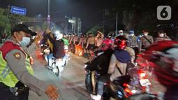 Polisi mengatur pemudik motor yang melintas di posko penyekatan mudik di Kedungwaringin, Kabupaten Bekasi, Jawa Barat, Selasa (11/5/2021) dini hari. Diskresi terhadap pemudik motor dilakukan sebagai langkah pencegahan mengurangi kerumunan. (Liputan6.com/Herman Zakharia)