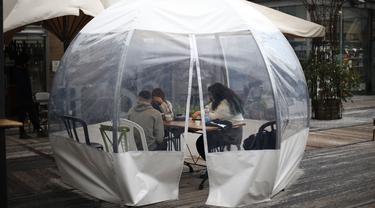 Sejumlah orang menyantap makanan di sebuah dining bubble, instalasi tempat makan berbentuk gelembung, di luar ruangan di Yerusalem pada 26 November 2020. Tempat makan di luar ruangan menjadi langkah yang diadopsi secara luas oleh banyak restoran untuk mengatasi pandemi COVID-19 (Xinhua/Muammar Awad)