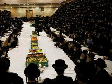 Sejumlah pria Yahudi Ultra-Orthodoks dari dinasti Belz Hasidic duduk sekitar meja makan yang sudah disediakan buah-buahan untuk memperingati perayaan Tu Bishvat, hari Arbor Yahudi di Jerusalem, (25/1).  (REUTERS/Ronen Zvulun)