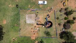 Pandangan aerial memperlihatkan Vernon Kruger, 52, duduk dalam tong di atas tiang berketinggian 25 meter di Dullstroom, 16 Januari 2020. Di dalam tong itu, ada pipa kecil untuk menyalurkan pembuangan hajat Kruger serta makanan yang diantarkan ke atas oleh tim dengan keranjang. (ANTOINE DEMAISON/AFP)