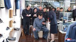 Pemimpin Korea Utara, Kim Jong-un melihat sepatu saat mengunjungi Taesong Department Store, setelah dibuka untuk umum di Korea Utara (8/4). (KCNA VIA AFP Photo)