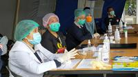 Petugas kesehatan Posko Tanggap Darurat Corona Covid-19 Kota Malang sebelum memeriksa kesehatan para santri yang baru pulang dari pondok pesantren pada Minggu, 29 Maret 2020 (Liputan6.com/Zainul Arifin)