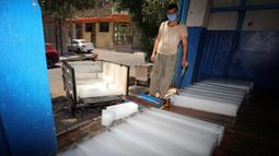 Seorang pria bekerja di sebuah pabrik pembuatan es di Baghdad, Irak, pada 5 Juli 2020. Seiring kenaikan suhu yang mendekati 50 derajat Celsius di Baghdad, bisnis pembuatan es di kota tersebut berkembang pesat dengan meningkatnya permintaan balok es. (Xinhua)