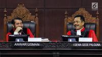 Hakim Konstitusi Anwar Usman dan I Dewa Gede Palguna tertawa saat sidang ke-5 sengketa Pilpres 2019 di Gedung MK, Jakarta, Jumat (21/6/2019). Sidang beragendakan mendengar keterangan saksi dan ahli dari pihak terkait yakni paslon nomor urut 01 Jokowi-Ma'ruf Amin. (Liputan6.com/Johan Tallo)