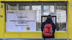 Seorang pasien saat di depan pintu masuk Stadion Signal Iduna Park, Jerman, Sabtu (4/4/2020). Stadion Borussia Dortmund ini dialihfungsikan menjadi tempat pusat pengujian COVID-19. (AP/Martin Meissner)