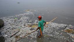 Pekerja mengumpulkan ikan mati yang hanyut ke daratan Freedom Island di sepanjang Teluk Manila, Filipina, Jumat (11/10/2019). Pekerja harus mengumpulkan ikan mati di antara sampah yang mencemari Teluk Manila. (Ted ALJIBE/AFP)
