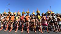 Perempuan pribumi berjalan kaki saat menggelar protes terkait kebijakan Presiden Brasil Jair Bolsonaro di Brasilia, Selasa (13/8/2019). Perempuan pribumi Brasil berdemonstrasi mengecam rencana Bolsonaro membuka hutan hujan Amazon untuk penambangan dan agribisnis. (EVARISTO SA/AFP)