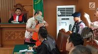 Korban ledakan bom di Jalan MH Thamrin pada Januari 2016, Ipda Denny Mahieu memeluk terdakwa Aman Abdurrahman di PN Jakarta Selatan, Jumat (23/2). Ipda Denny menjadi saksi kasus terorisme dengan terdakwa Aman Abdurrahman. (Liputan6.com/Ady Anugrahadi)