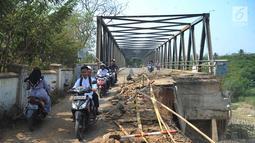 Pengendara motor melintasi jembatan Cipamingkis Cibarusah, Kab Bekasi, Jawa Barat (15/7). Jembatan tersebut merupakan penghubung dengan tiga Desa Sirnajati, Ridogalih, dan Ridomanah dengan kawasan Jonggol, Bekasi dan Cileungsi. (Merdeka.com/Arie Basuki)