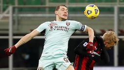 Striker Torino, Andrea Belotti, duel udara dengan pemain AC Milan, Simon Kjaer, pada laga Liga Italia di Stadion San Siro, Sabtu (9/1/2021). AC Milan menang dengan skor 2-0. (AP/Antonio Calanni)