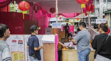 Warga mendaftar saat akan mencoblos di TPS 08 Petak Sembilan, Glodok, Jakarta, Rabu (17/4). TPS 08 Petak Sembilan mengambil tema budaya Tionghoa untuk menarik minat pemilih dan menekan angka golput. (Liputan6.com/Faizal Fanani)