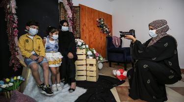 Seorang wanita dan anak-anak mengenakan masker berpose saat difoto  pada liburan Idul Fitri Muslim selama pandemi virus coronavirus COVID-19 di studio foto Palestina Faten Issa's studio di Rafah di Jalur Gaza selatan (27/5/2020). (AFP/Said Khatib)