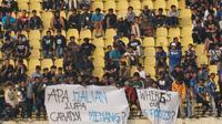 Bobotoh membentangkan spanduk sebagai kritik atas permainan Persib Bandung saat melawan Bhayangkara FC, Minggu (30/6/2019. (Liputan6.com/Huyogo Simbolon)