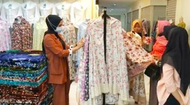 Emak-emak memilih mukenah raga motif yang dijual di pasar Pekanbaru.