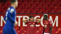 Pemain Manchester United, Edinson Cavani, berbincang dengan Paul Pogba saat pertandingan melawan Chelsea pada laga Liga Inggris di Stadion Old Trafford, Minggu (25/10/2020). Kedua tim bermain imbang 0-0. (Oli Scarff/Pool via AP)