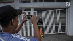 Warga mengambil gambar pintu masuk zona 9 Stadion Utama Gelora Bung Karno yang rusak, Jakarta, Minggu (18/2). Ratusan Jakmania yang tak memiliki tiket memaksa masuk hingga menjebol pintu di stadion saat final Piala Presiden. (Liputan6.com/Faizal Fanani)