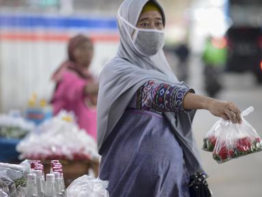 Pedagang menawarkan kembang untuk berziarah di kawasan Gembrong, Prumpung, Jakarta, Kamis (23/4/2020). Jelang Ramadan, pedagang kembang untuk berziarah mengeluhkan sepinya pembeli karena adanya Pembatasan Sosial Berskala Besar (PSBB) untuk mencegah penyebaran COVID-19. (merdeka.com/Imam Buhori)