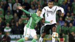 Gelandang Irlandia Utara, Shayne Lavery, berusaha melewati bek Jerman, Jonathan Tah, pada laga Kualifikasi Piala Eropa 2020 di Windsor Park, Belfast, Senin (9/9). Irlandia Utara kalah 0-2 dari Jerman. (AFP/Paul Faith)